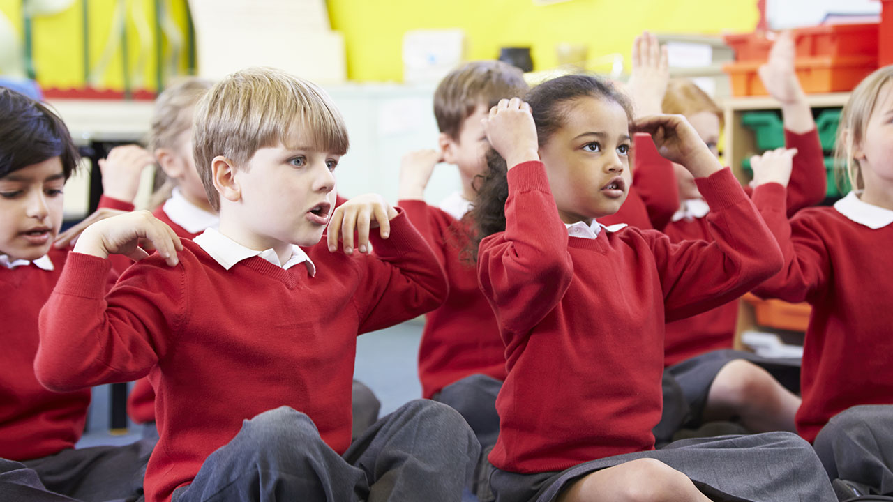 Schoolchildren singing heads, shoulders, knees and toes